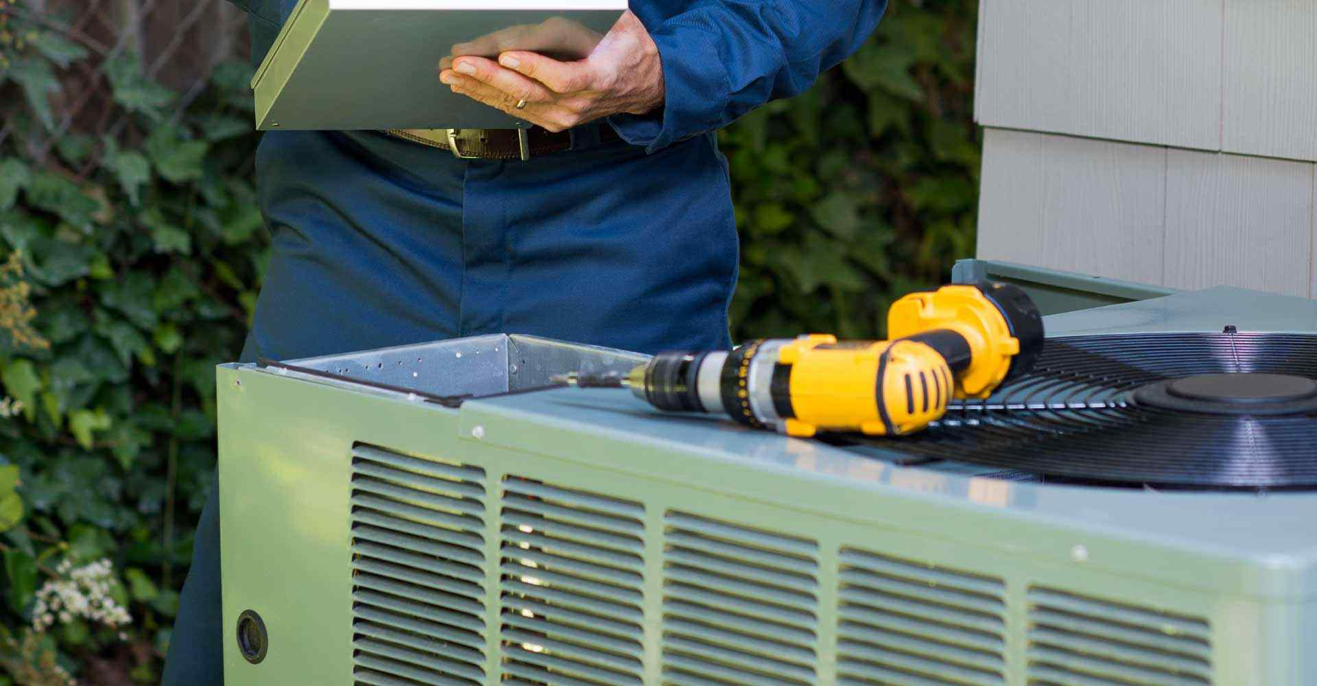 HVAC expert fixing an air conditioning unit on a call provided by his phone answering service