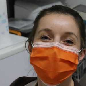 A nurse wearing a surgical mask, knowing that an answering service is taking her calls